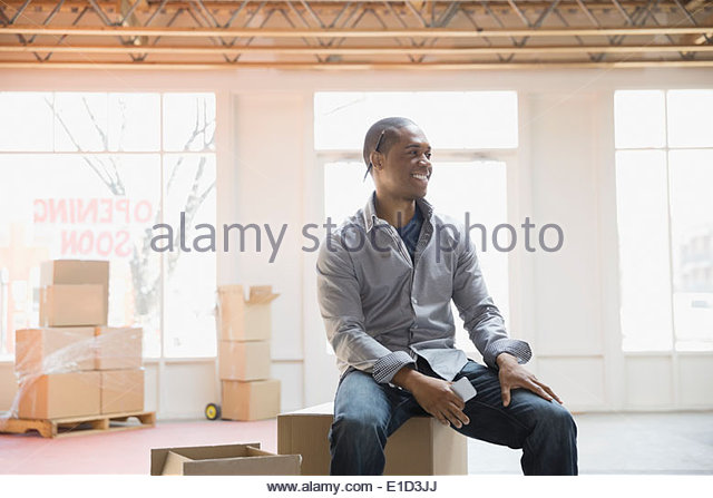 Businessman sitting on cardboard box in new office - Stock Image