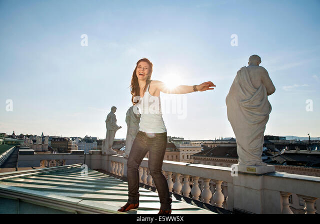 Young adult woman laughing, on rooftop, Vienna, Austria - Stock Image