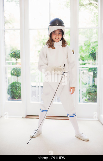 Girl wearing fencing gear in living room - Stock Image