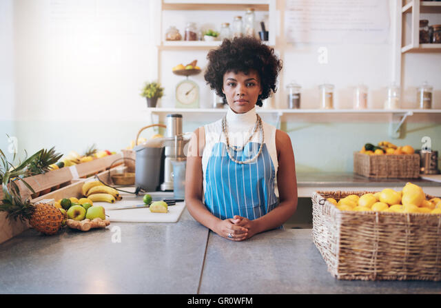 Portrait of young african woman wearing apron standing behind juice bar counter looking at camera. - Stock Image