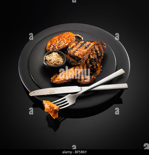Barbecued sweet potato with sesame seeds, on a black background. - Stock Image