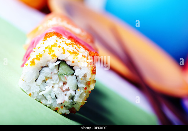 Close-up horizontal photo of the rolled sushi with rice and cucumber on the table. Vibrant color and shallow depth - Stock Image