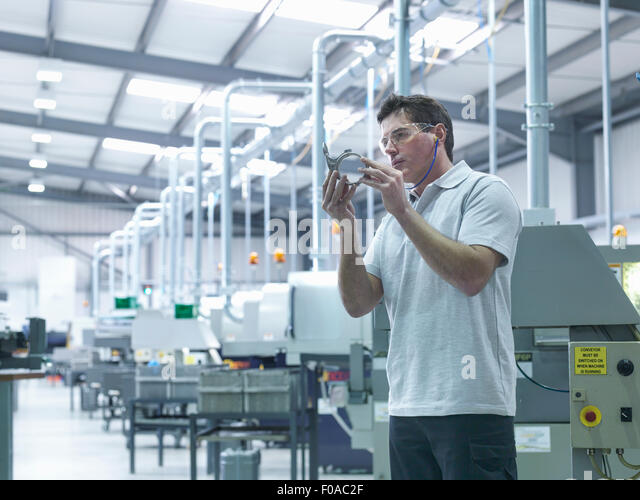 Engineer inspecting part on production line - Stock Image