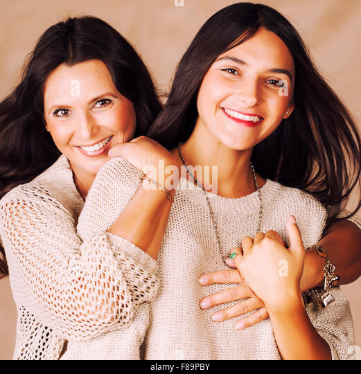 cute pretty teen daughter with mature mother hugging, fashion style brunette makeup close up tann mulattos - Stock Image