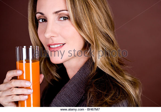 A mid adult woman holding a glass of fruit/carrot juice - Stock Image