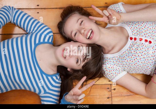 Girls lying on wooden floor doing peace signs - Stock-Bilder