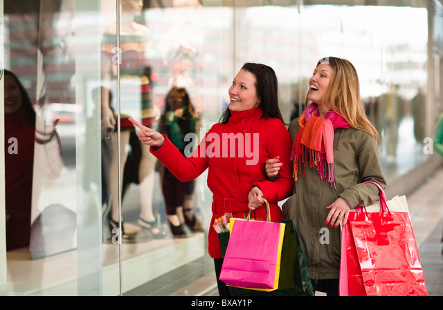 Pair of young women window shopping - Stock Image