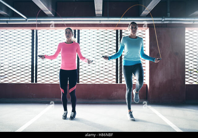 Front view of two athletic girls doing jump rope exercise. Copyspace - Stock Image