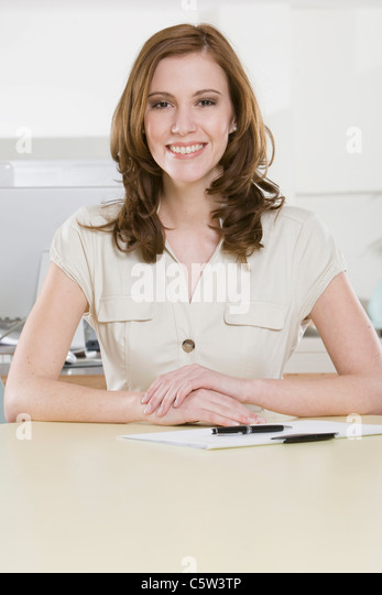Germany, Munich, young woman in office, smiling, portrait - Stock-Bilder