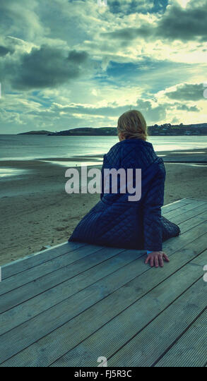 young woman sitting on wood on beach - Stock Image