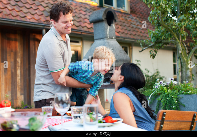 Family having dinner in garden - Stock-Bilder