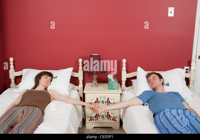 Young couple lying on single beds, holding hands - Stock Image