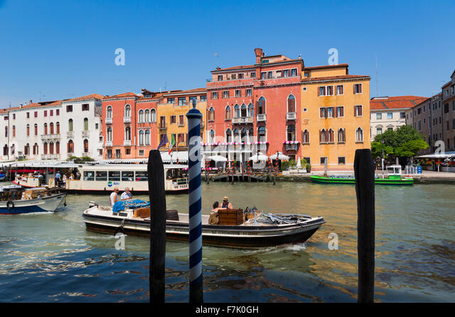 Venice, Italy.  Traffic on the Grand Canal.  Boats delivering goods.  In background, a vaporetto, or waterbus. - Stock Image