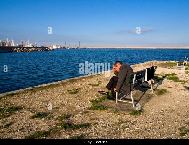 Man sitting on a bench along the marina Palermo Sicily Italy - Stock Image