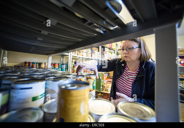 A volunteer working in a food bank. - Stock Image