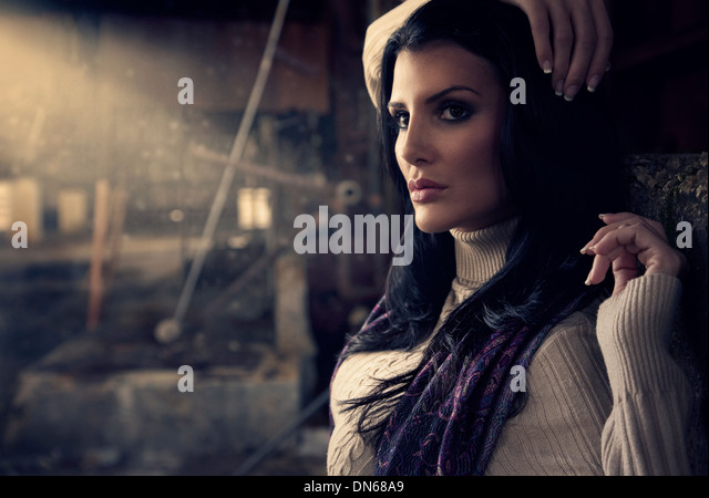 Fashion portrait of woman in abandoned warehouse with light beam - Stock Image