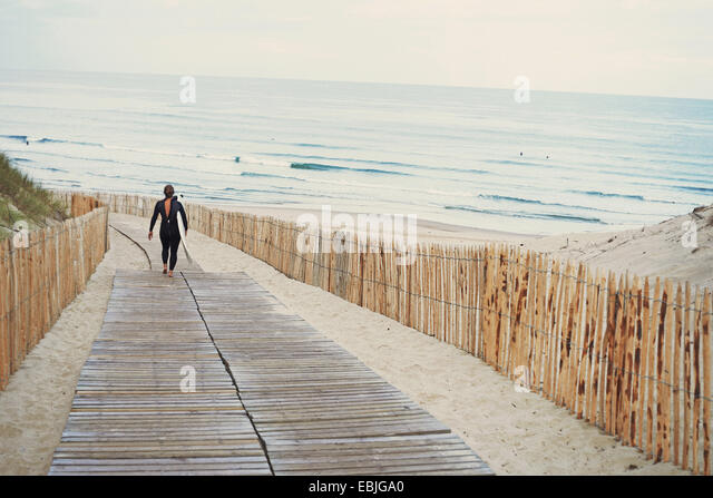 Surfer with surfboard walking to beach, Lacanau, France - Stock Image