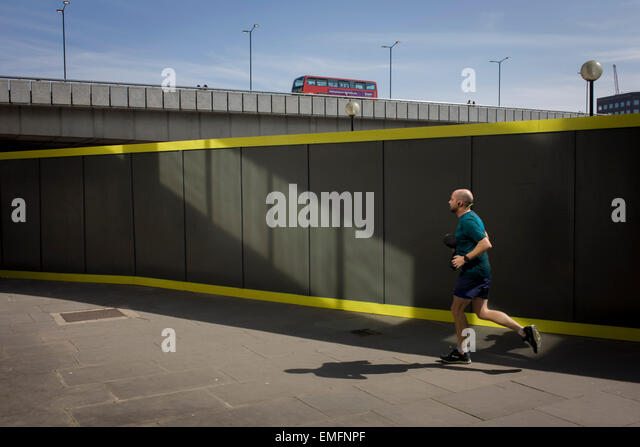 Lunchtime jogger runs past hoarding with London Bridge in the background. - Stock-Bilder
