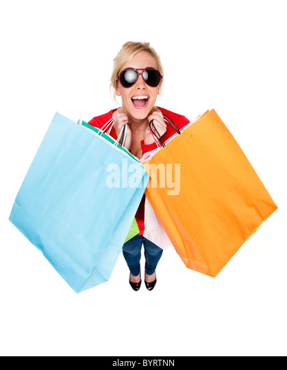 Attractive young woman wearing sunglasses looking happing holding multi-coloured shopping bags - Stock Image