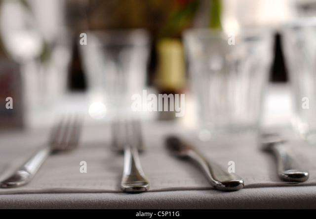 Knives and forks on grey - Stock Image