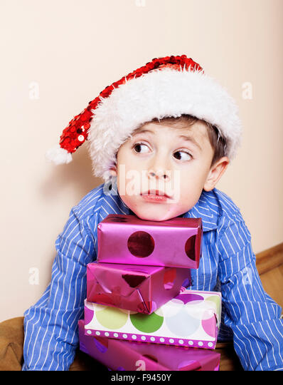 little cute boy with Christmas gifts at home. close up emotional face on boxes in santas red hat - Stock Image