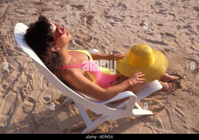 Beach Woman Relaxing in Beach Chair with hat - Stock Image