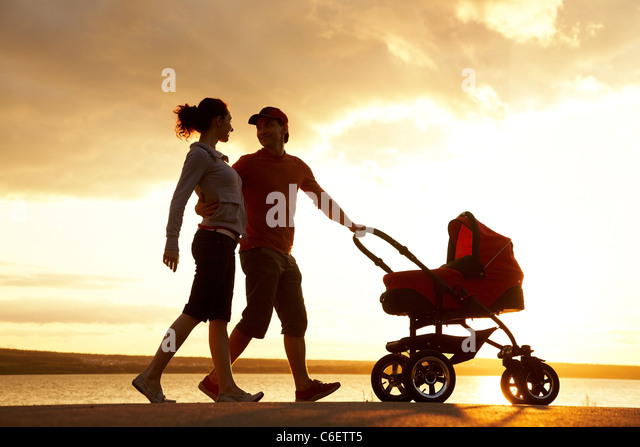 Silhouettes of happy parents walking with stroller on the seacoast - Stock-Bilder