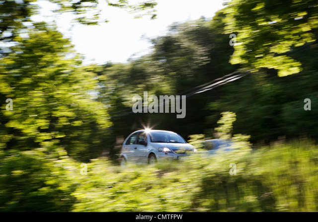 Car moving in speed at forest - Stock Image