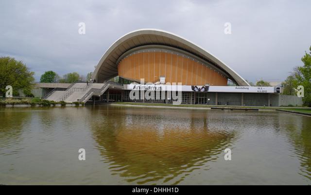 Grey clouds view orange parabolic roof 'Haus der Kulturen der Welt' reflecting lake waters, Tiergarten Park, - Stock-Bilder