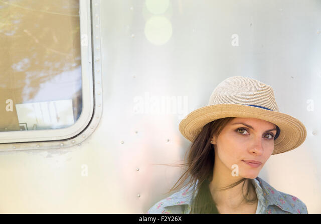 A young woman wearing a hat sitting in the shade of a silver coloured trailer. - Stock Image