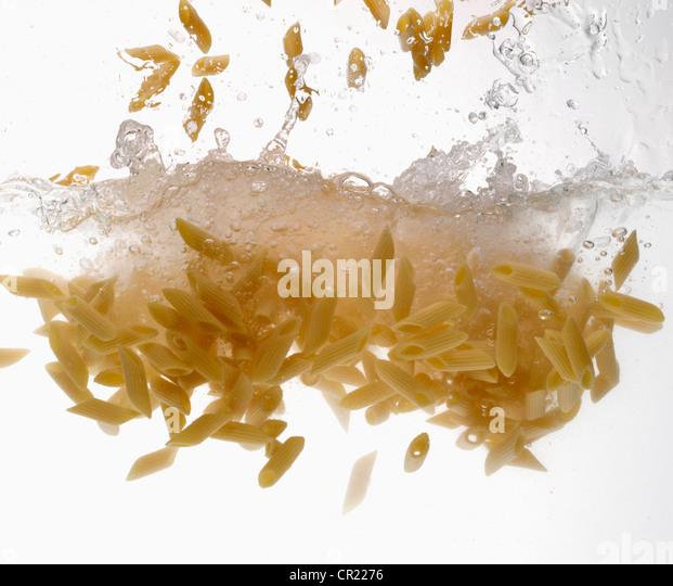 Pasta splashing in water - Stock Image