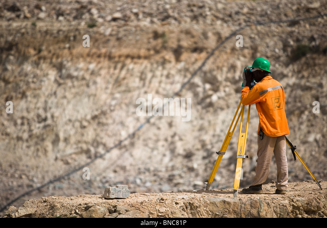A mine worker surveys at the Youga gold mine near the town of Youga, Burkina Faso. - Stock Image