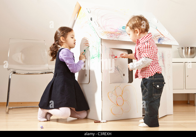 Boy and girl painting cardboard house - Stock Image