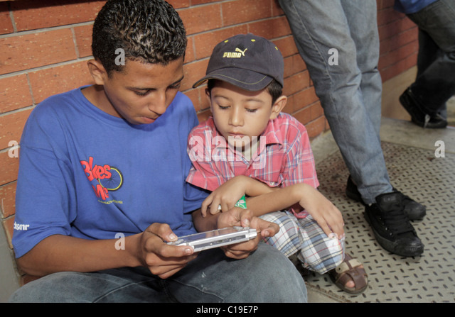 Panama Panama City Amador Hispanic boy teen handheld video game interactive electronic game younger older concentration - Stock Image