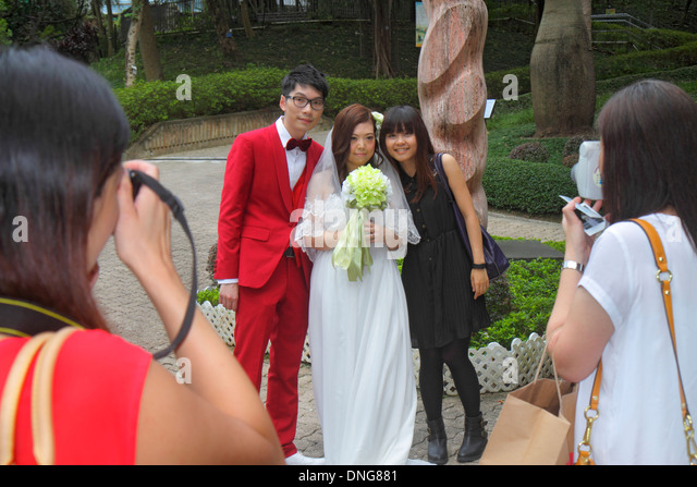 Hong Kong China Island Central Hong Kong Park wedding photographer photos bride groom posing red suit dress Asian - Stock Image