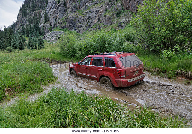 jeep going through flooded road in colorado - Stock Image