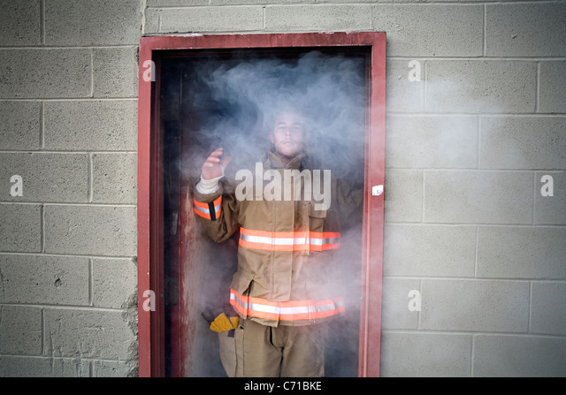 young firefighter stands in smokey doorway - Stock Image
