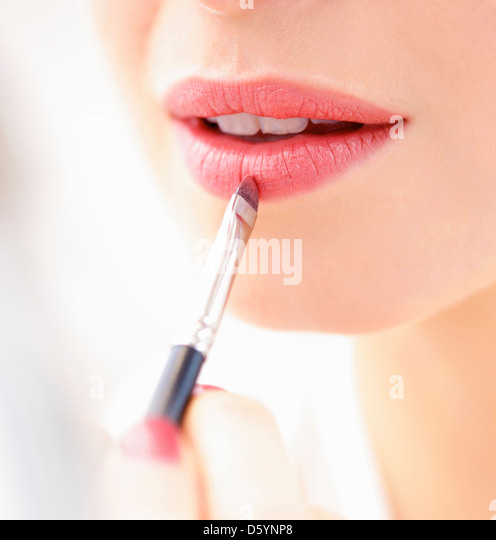 Woman Applying Lipstick with Makeup Brush, Close-up View - Stock Image