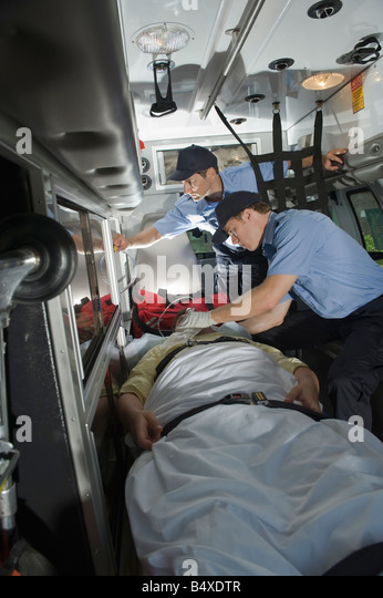 EMT's caring for patient in ambulance - Stock Image