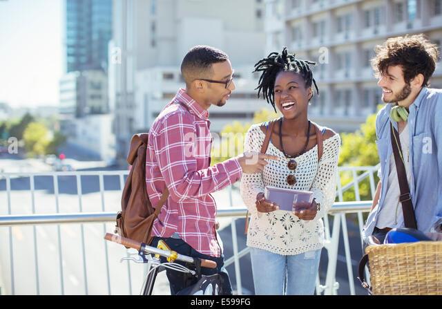 Friends talking on city street - Stock Image