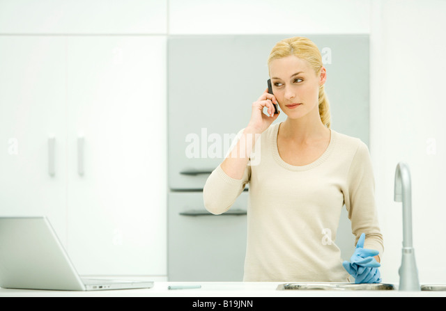 Young woman standing in kitchen, holding rubber gloves, using cell phone - Stock-Bilder