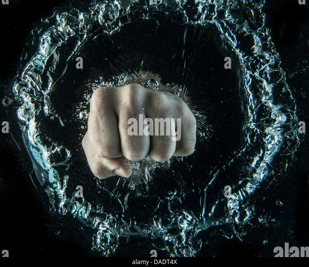 Close up of clenched fist beneath water - Stock Image