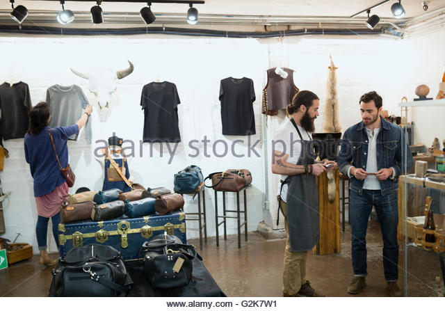 Leather shop owner assisting customer - Stock Image