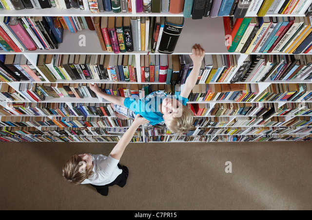 Girl helping boy climb bookshelves - Stock Image