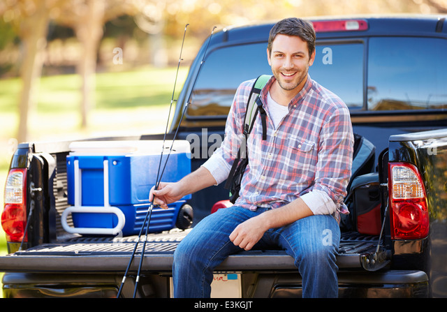 Man Sitting In Pick Up Truck On Camping Holiday - Stock Image