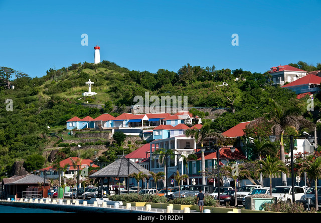 Downtown Gustavia along the waterfront quay with hill and red-roofed buildings, Saint Barthelemy - Stock Image