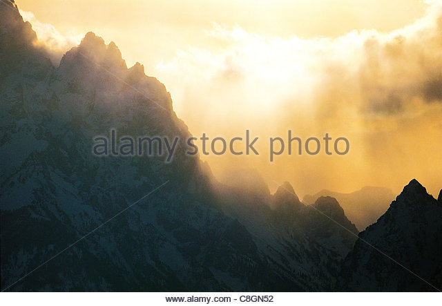 An overview of Rocky Mountain peaks at sunset with rain clouds. - Stock Image