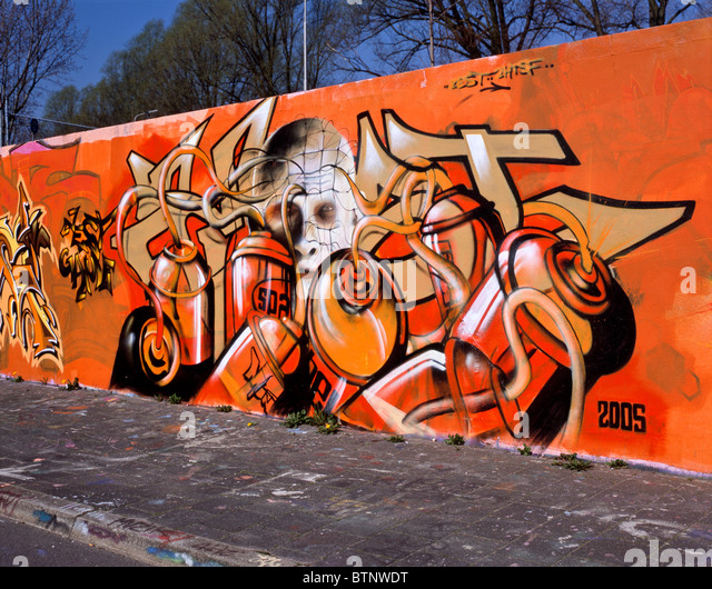 Graffiti showing spray cans in the foreground and a pale white face covered with a net in the background, Delft, - Stock Image