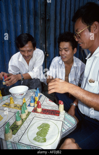 Vietnam Saigon Ho Chi Minh City Asian men play board game sidewalk - Stock Image