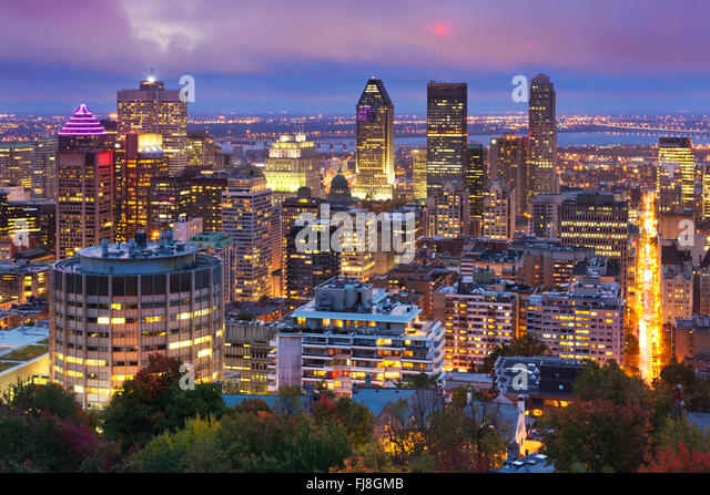 The skyline of downtown Montréal, Quebec, Canada from the top of Mount Royal. Photographed at dusk. - Stock Image